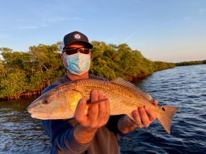 Fishing w/King Fisher Fleet, Man holding redfish, wearing a mask