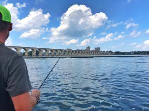Man fishing next to a bridge on the Susquehanna River