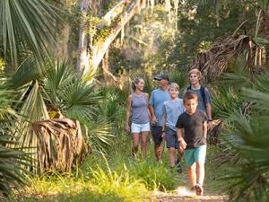 Smiling family enjoying a hiking trails in Daytona Beach