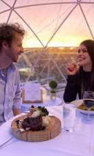 A couple dining in a rooftop igloo at sunset.