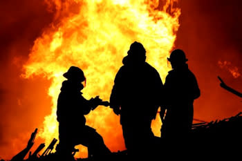 Firefighter silhouettes with fire in background