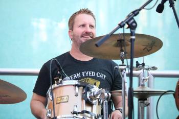 Drummer sitting at drum set at outdoor concert