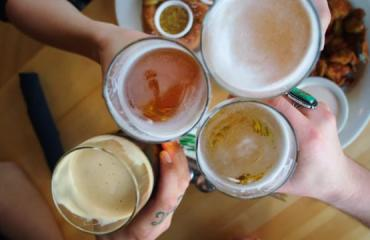 4 patrons holding their beer up in a toast at a brewery in Salt Lake City
