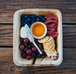 Overhead view of a Cheese Plate with blueberries, grapes, salami, crackers, honey and cheeses