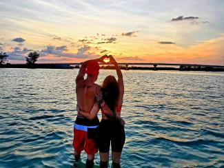 """Couple standing in water at sunset, creating """"heart hands"""""""