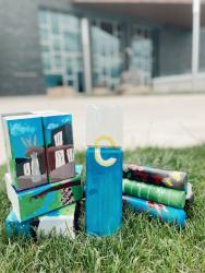 """Stacked kubb featuring artist painting of Pablo Center and Eau Claire yellow """"e"""" logo set on ground outside with Pablo Center in background"""
