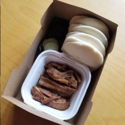 A to-go box of meat and buns from Morris Ramen