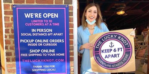 Woman holding a Lucky Knot Covid-19 Opening Rules sign in Alexandria, VA
