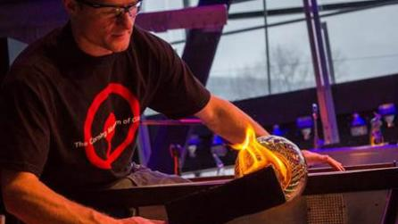 A glassblower shaping glass at the Corning Museum of Glass