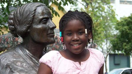 Girl at Susan B Anthony Museum and statue
