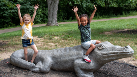 two children sitting on concrete alligator with their hands in the air, enjoying playing at Florence nature park in Florence ky