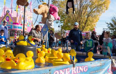A family playing carnival games at the Clayton Harvest Festival in Johnston County, NC.