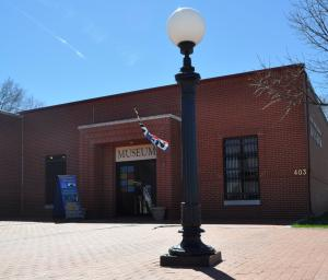 Exterior of the Finney County Historical Museum, a red brick building with an antique light post in front