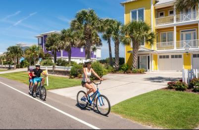A family biking past beach houses in Kure Beach