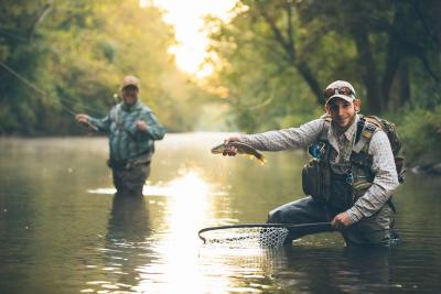 Man Holding Up Caught Fish With Friend in Background in Cumberland Valley
