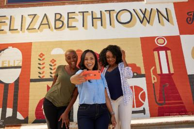 3 girls taking a selfie in front of a mural