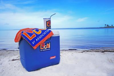 a orange t-shirt with a local by association logo laid across a blue cooler with a local by association sticker, and a cup with a local by association sticker on the cooler.