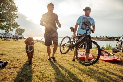 A labradoodle on a leash next to its owner and a man with a mountain bike