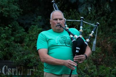 Man playing bagpipes with trees behind him