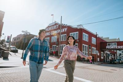 Smiling man and woman walk along Monterey County's Cannery Row.