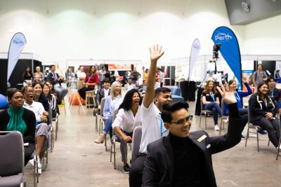 A group of delegates raising their hands in an exhibition hall