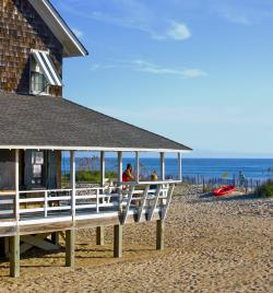 Visitors enjoy the fresh air and view from the wrap-around porch of their Outer Banks vacation rental.
