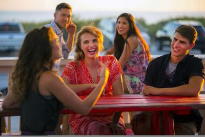 Millennials laughing and dining at sunset