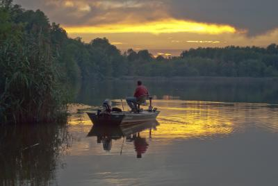 A fisherman enjoys the morning sunrise over the water at Lums Pond State Park.