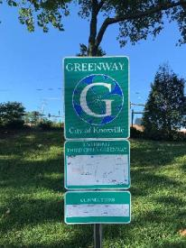 A sign advises visitors about the City of Knoxville Greenway path.