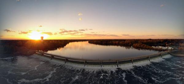 A panoramic view of a sunset over the dam and lake at Mississippi Gateway Regional Park