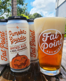 Cans and a glass of Fat Point Brewing's Pumpka Gourda Ale on a table with blue sky in the background