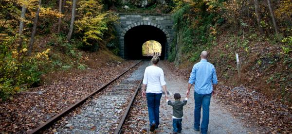 A small child holds hands with their parents as they walk along the rail trail toward Howard Tunnel in fall