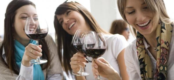 Three young women laugh as they raise their glasses of red wine for a toast