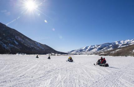 Group of snowmobiles in a wide-open field in Weber Canyon on sunny day.