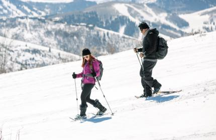 Couple snowshoeing down hill with ski resort in background