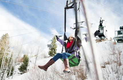 Woman sliding down zipline in winter at Utah Olympic Park