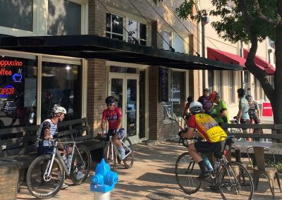Cyclists gather in front of Cadence Cyclery shop