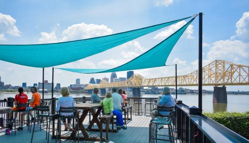 People sitting on the outdoor patio under sun shades at Upland Brewing in Jeffersonville, IN