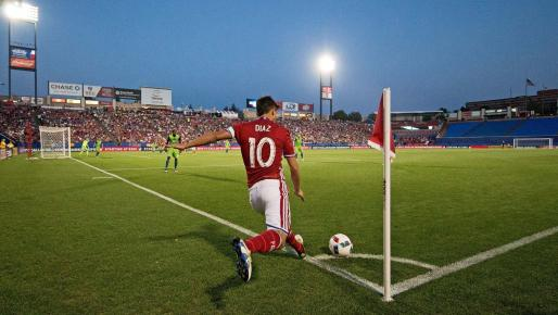 Player for FC Dallas kicking a corner kick during a soccer game at night
