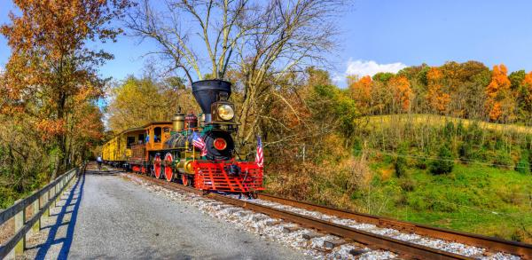 A steam engine makes it's way through a fall scene.