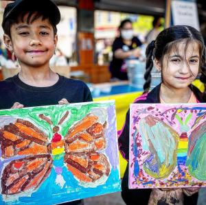 Boy and girl holding paintings of butterflies