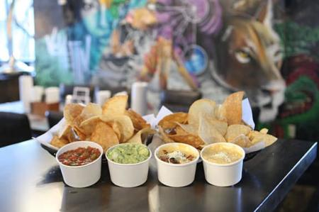 two baskets of chips in front of artwork on wall with cups of salsa, guacamole, queso at agave and rye in covington ky