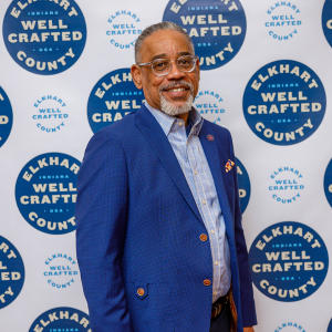 Arvis Dawson poses in front of a white backdrop with the words Elkhart County Well Crafted in blue circles