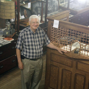 Local historian John Hertzler stands at an old-fashioned ticket booth in the Goshen Historical Museum in Goshen, Indiana.