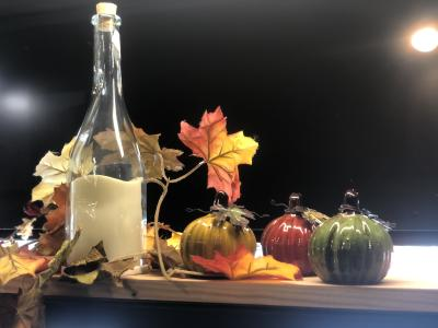 Glass colored pumpkins on a table with fall leaves from Threadz