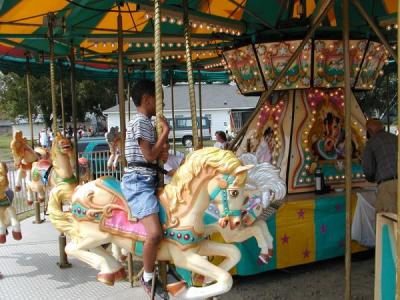 A child riding on a merry-go-round at the Clayton Harvest Festival in Clayton, NC.