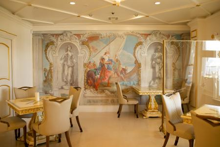 Image of one of Anaheim White House restaurant's dining rooms. The room includes a mirror on the back wall with three tables. The room is white with plenty of gold accents. The dining tables are also white with a gold pattern. The chairs are beige.