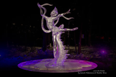 a large lighted ice sculpture of a dancer outdoors