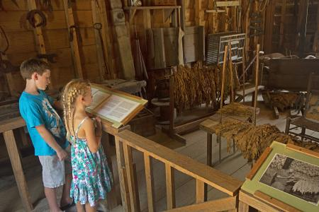 Two children stand at an interactive barn exhibit to read the information on the plaque at the Tobacco Farm Life Museum in Kenly, NC