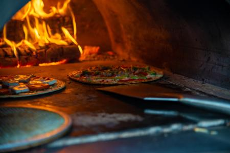 Fresh made pizzas cooking in a wood-burning oven